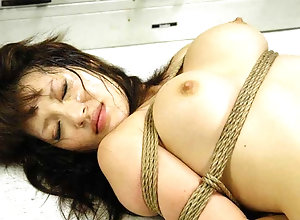 Bound Asian cutie gets fucked with behind the bars