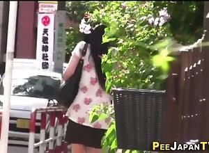 Asian babe urinates outdoors